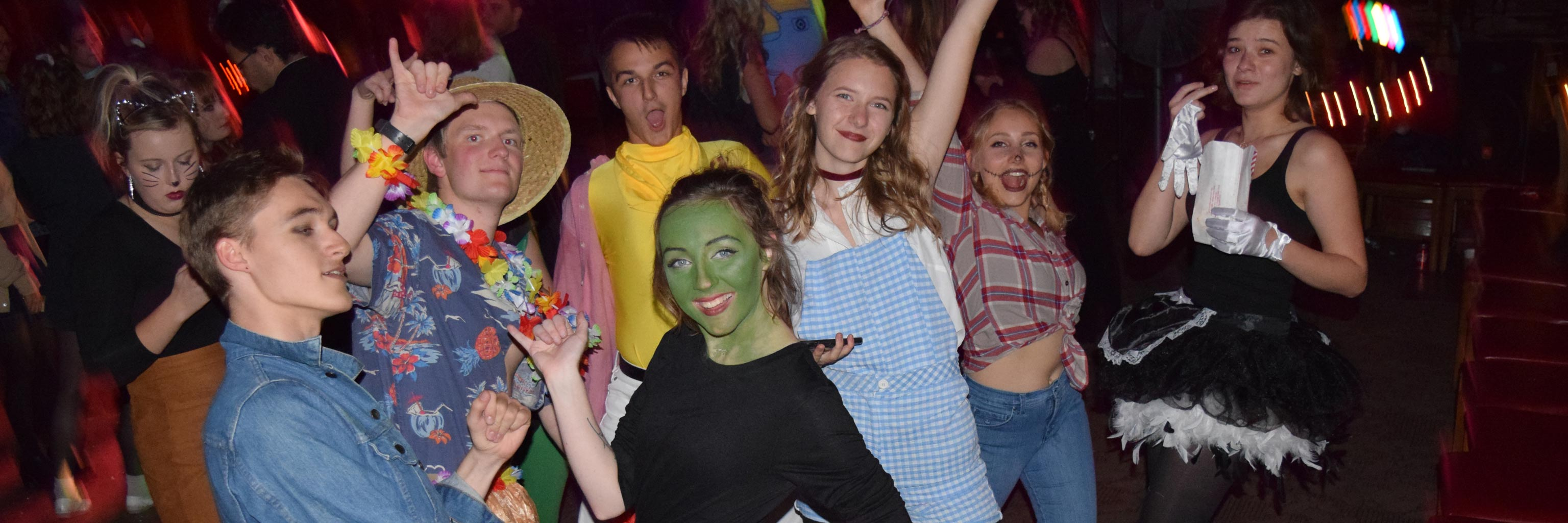 A group of students dance and pose for the camera at a costume party