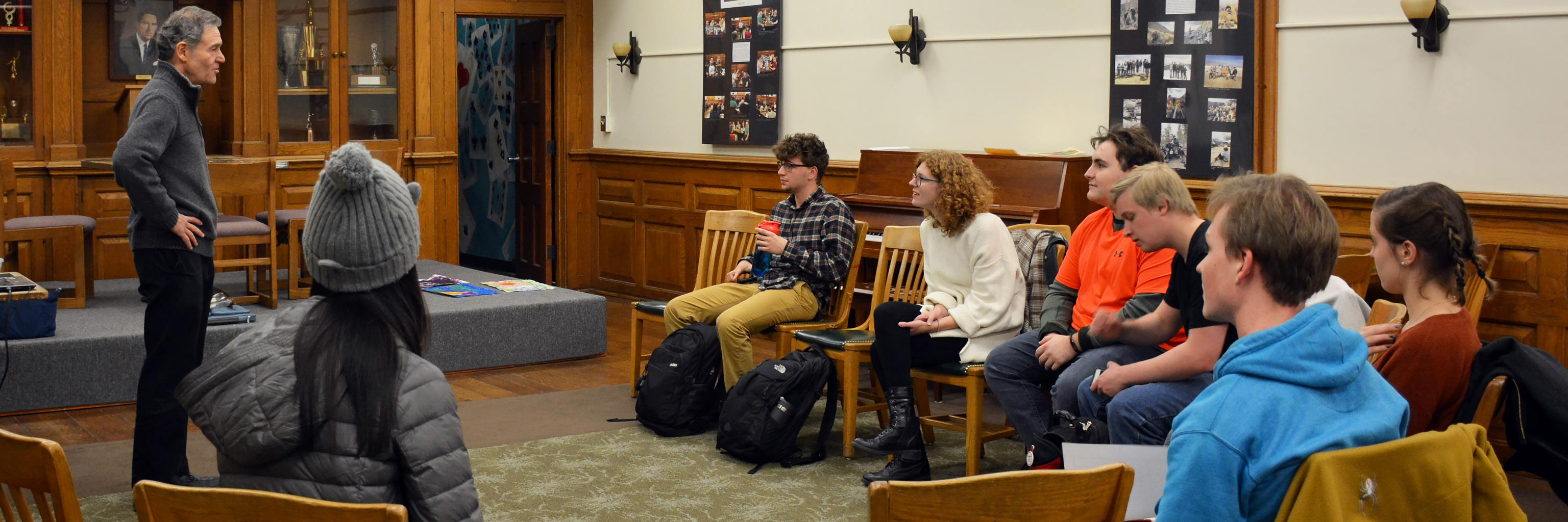 A professor lectures to a small group of engaged students