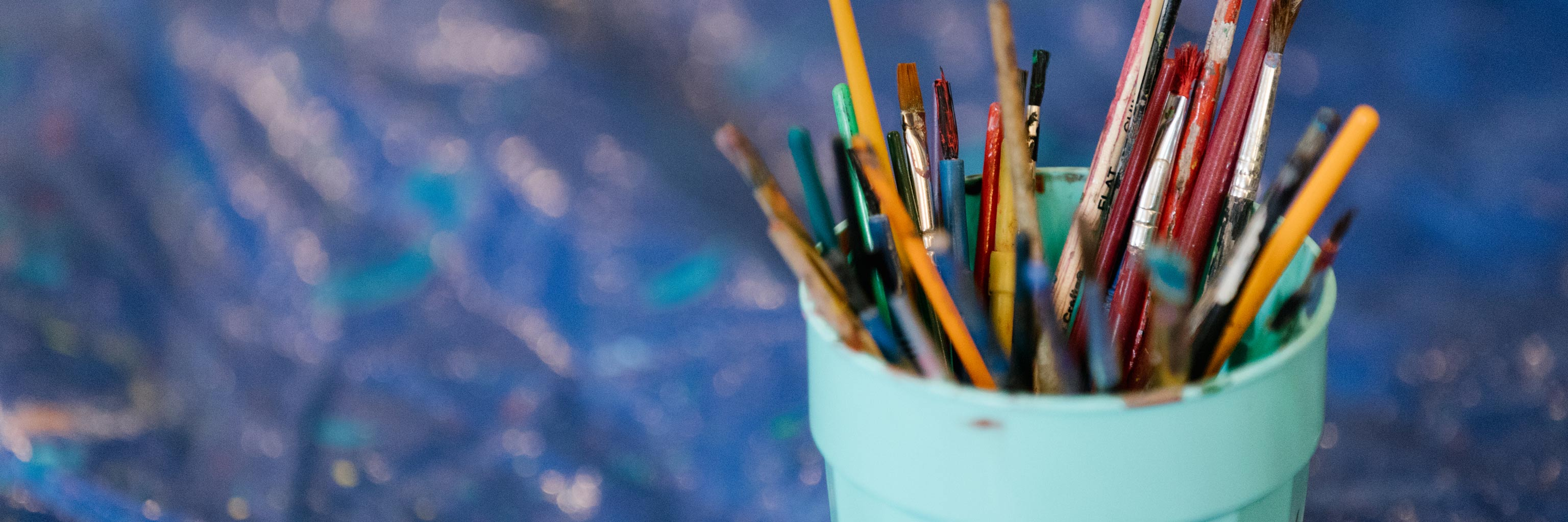 Close up of a cup full of paint brushes