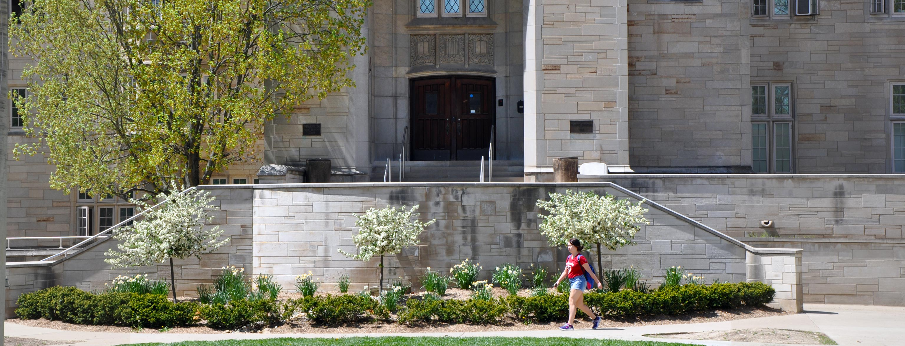 A student walking by the steps to the main entrance of the Collins Center