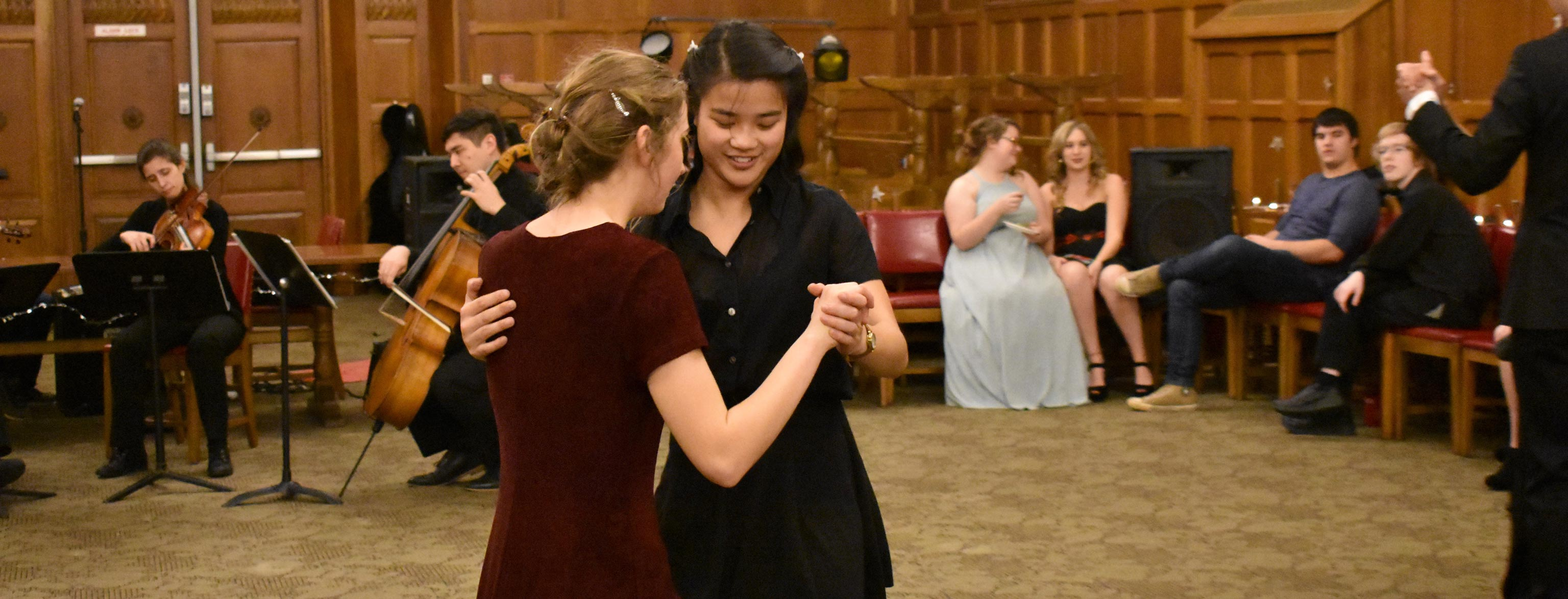 Two female students dance hand-in-hand