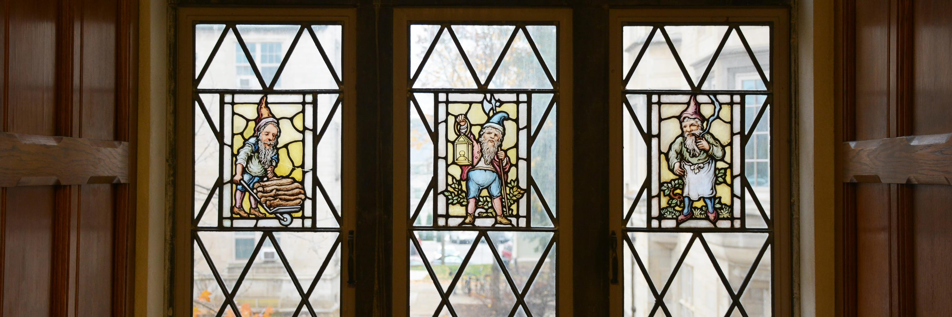 Three stain glass windows side-by-side, each containing an image of a gnome