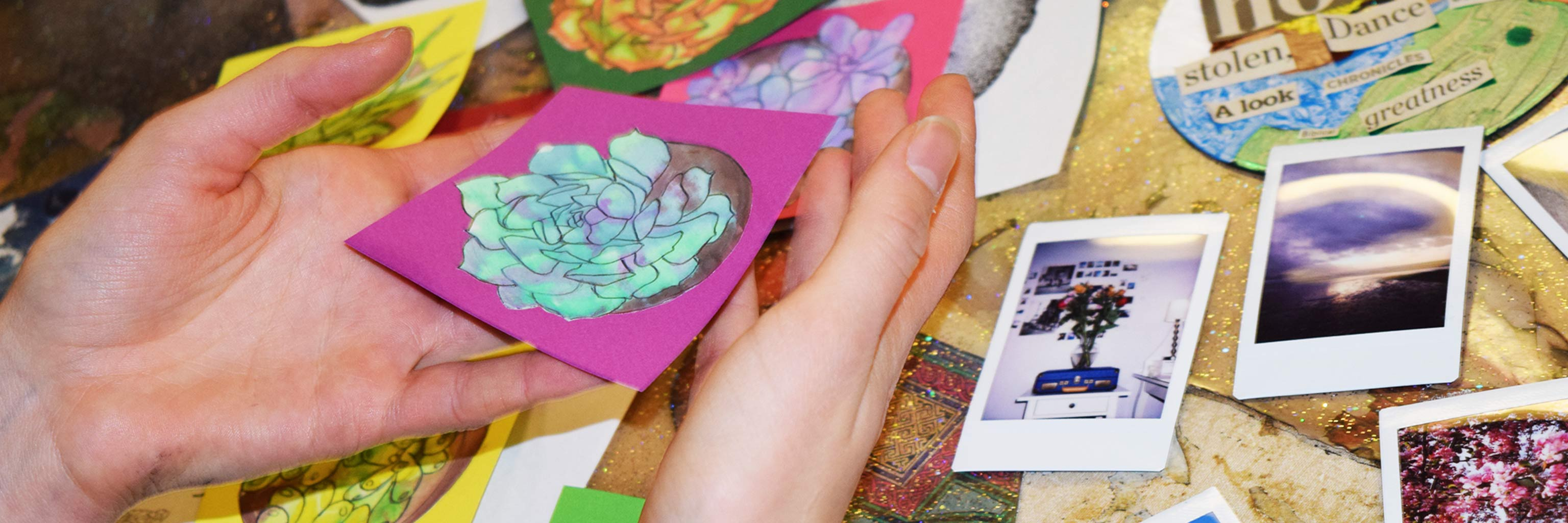 Close up of a pair of hands cradling a small painting of a flower