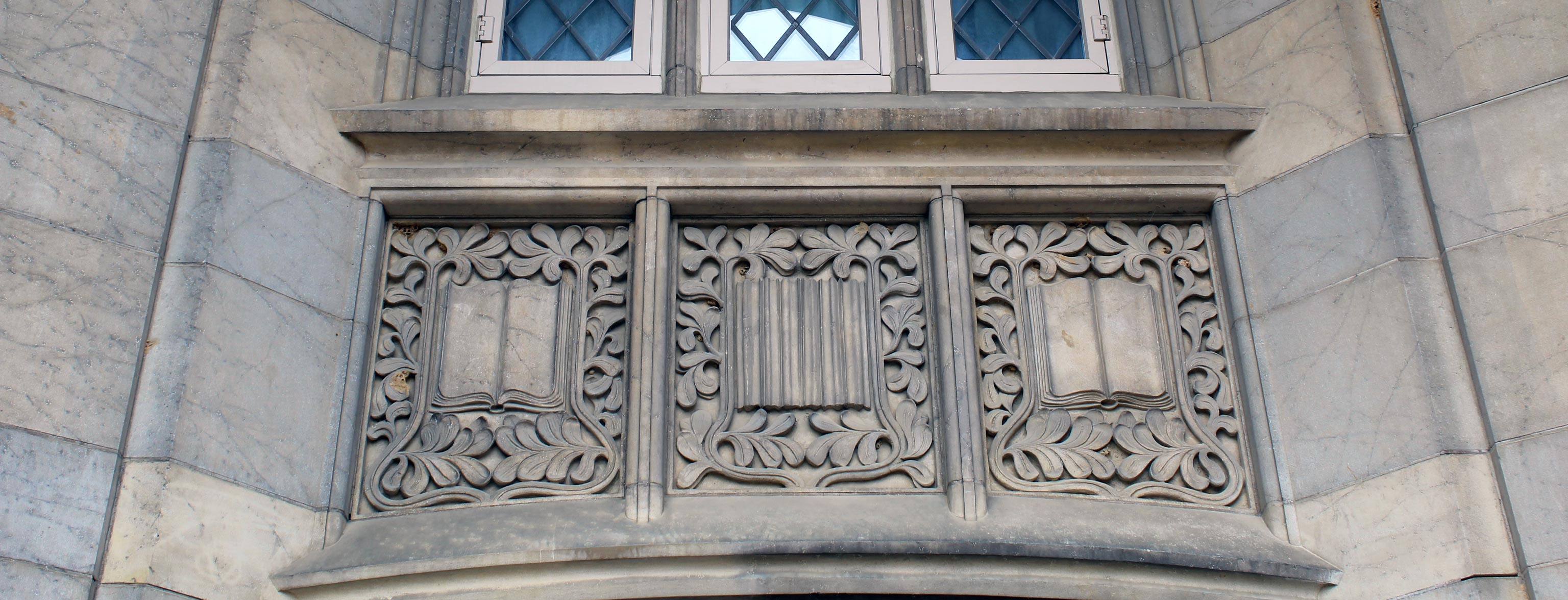 Ornate carvings beneath a window on the exterior of a limestone building