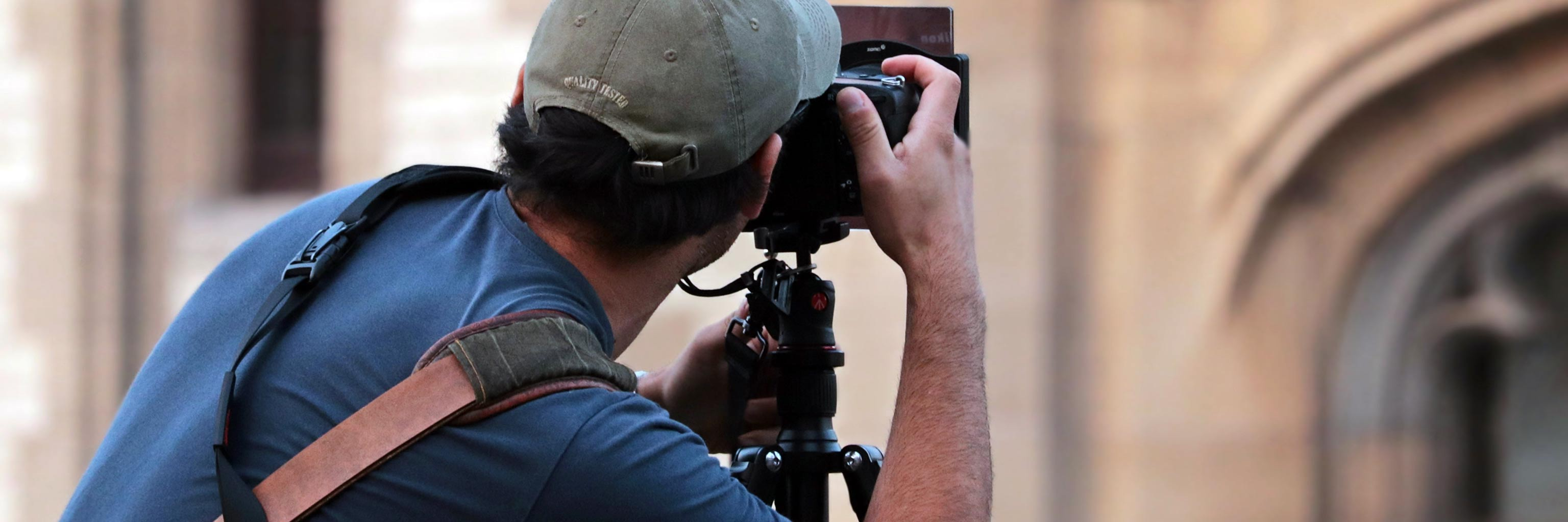 A man in a baseball cap with his back to the viewer  holds a camera up to take a picture of a limestone building