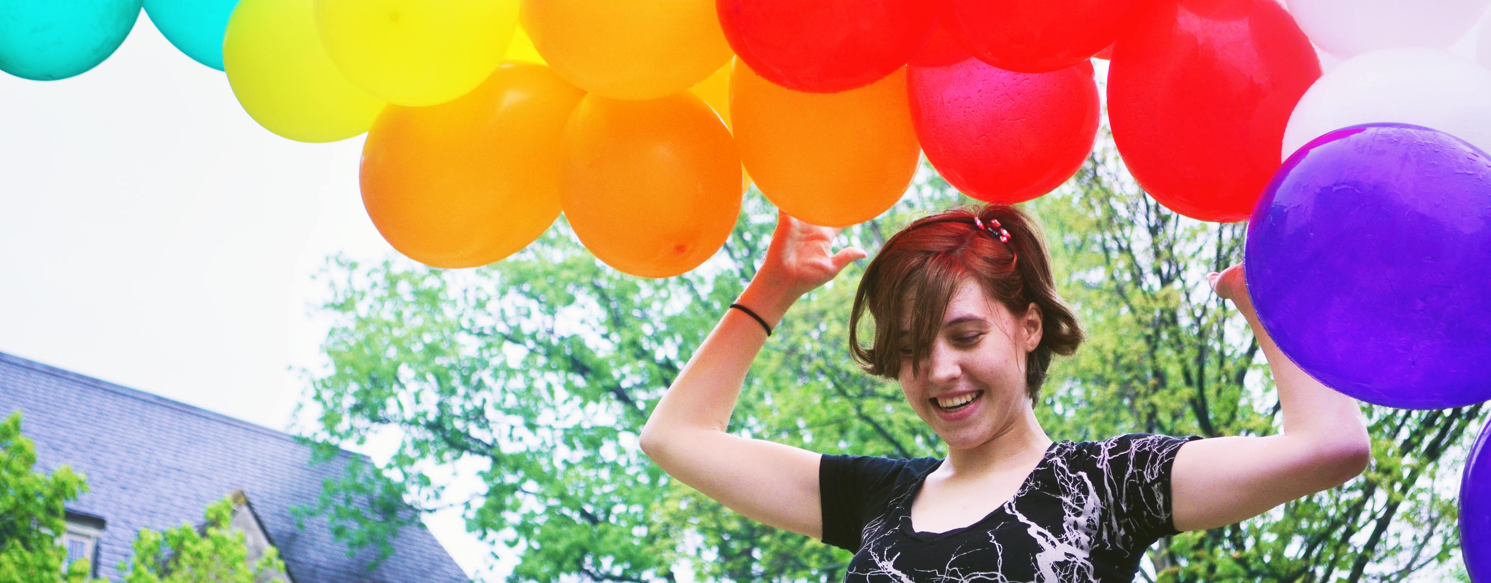 Brunette female student smiles while holding a large bunch of colorful balloons