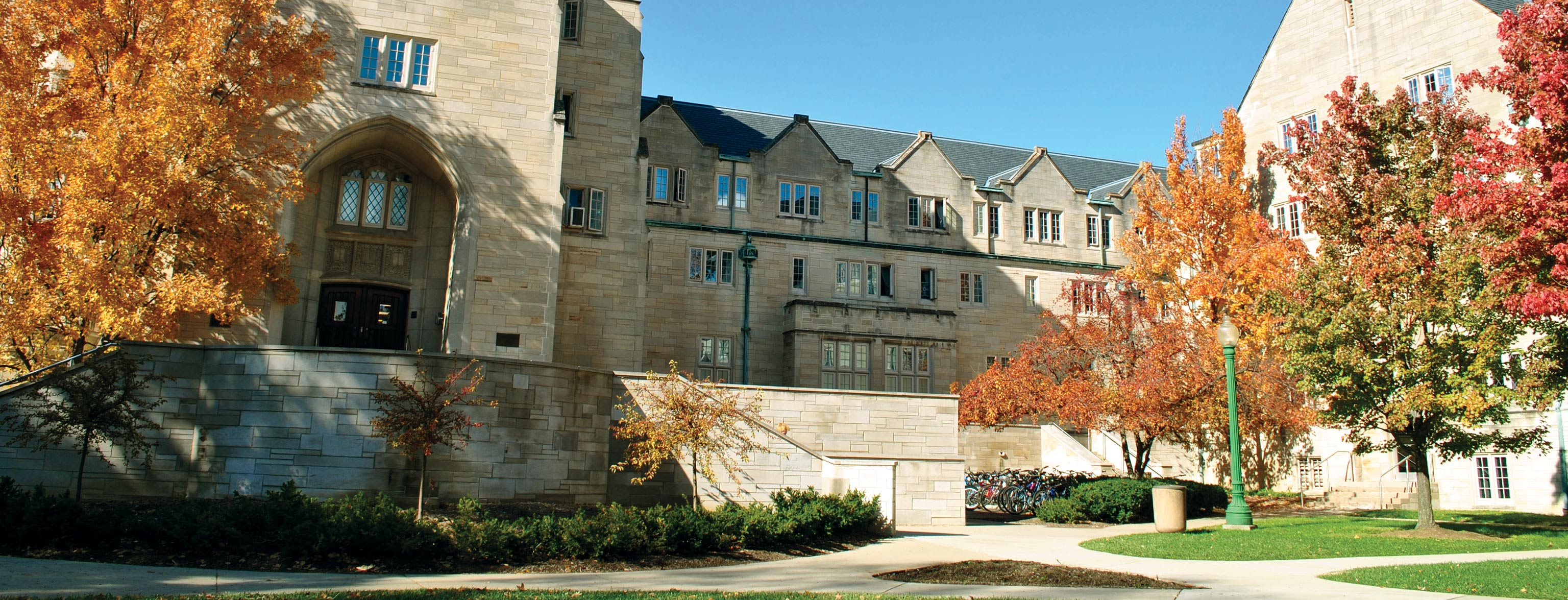 The exterior of Collins Living-Learning Center in the fall when the leaves on its courtyard trees are red. orange, and green