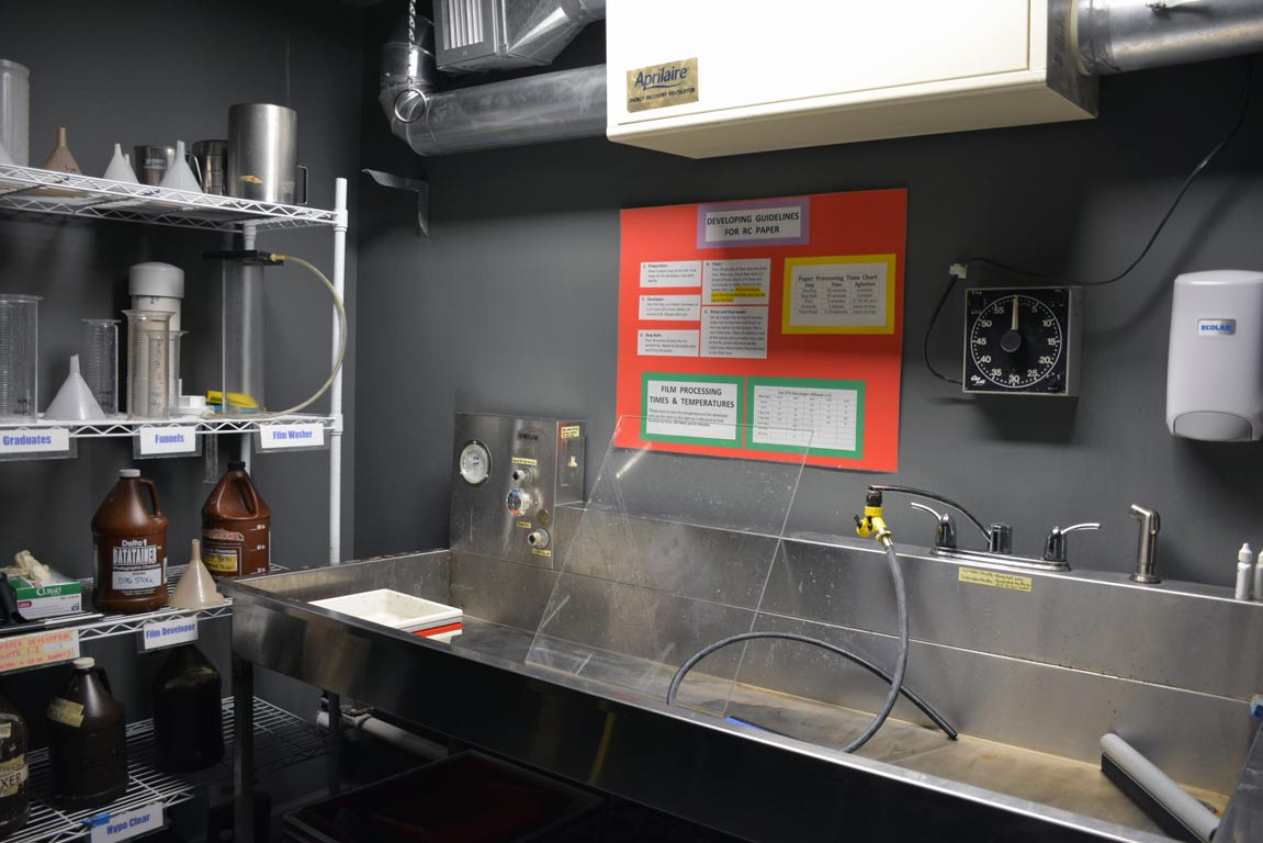 A large sink and shelf of supplies in the photography darkroom
