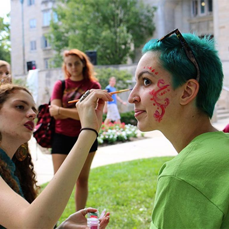A student sits and has her face painted with an elaborate pink design by another student