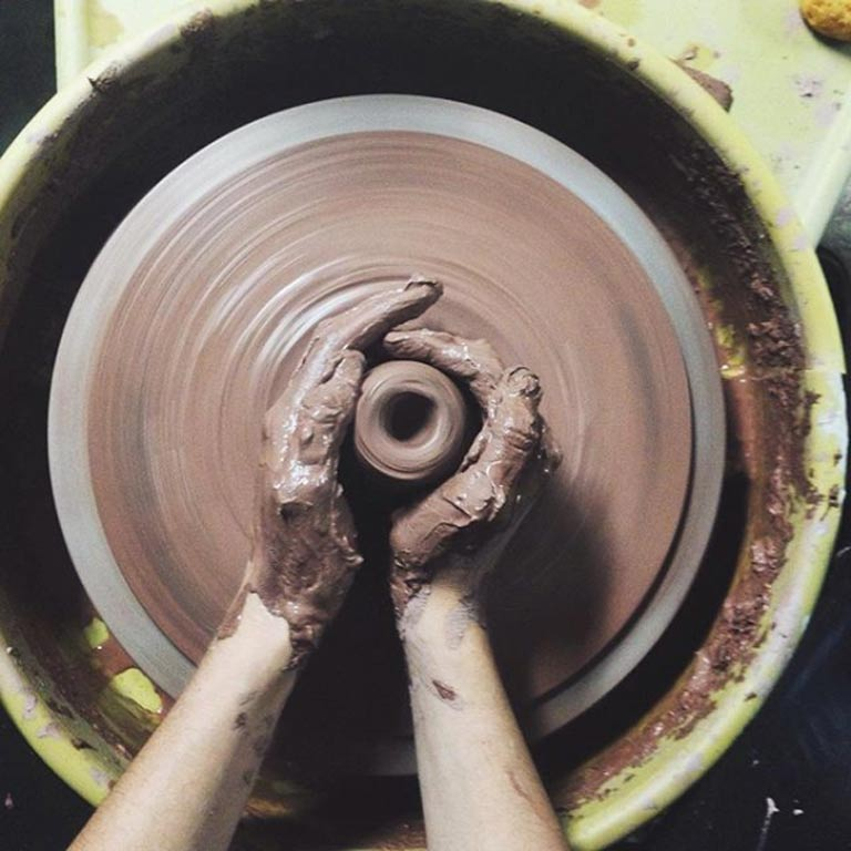 A pair of hands working to form clay pottery