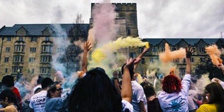 Students in front of the Collins Center throw colored powdered into the air