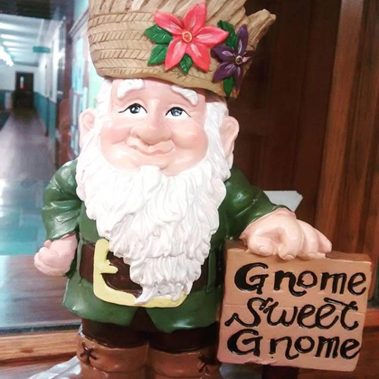 "Small gnome statue holding a sign that reads, ""Gnome sweet gnome"""