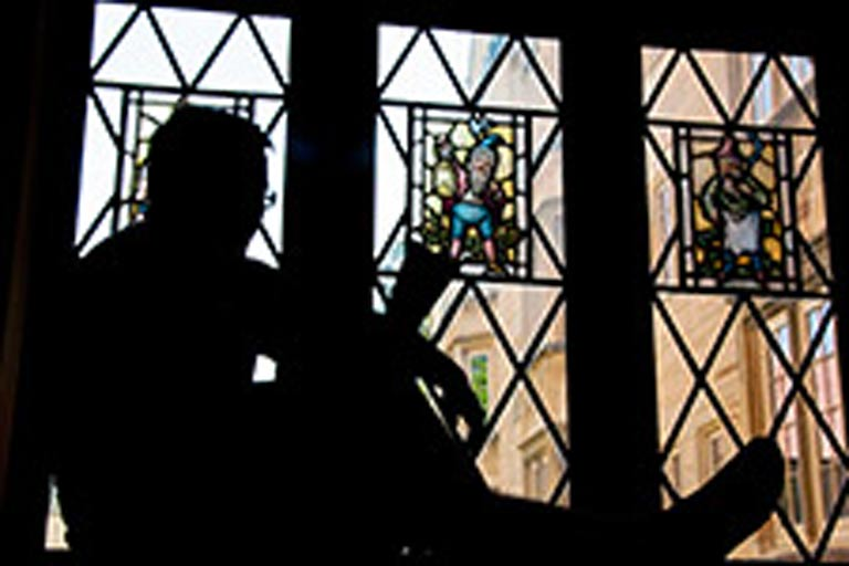 Silhouette of a student reading in front of three stain glass windows