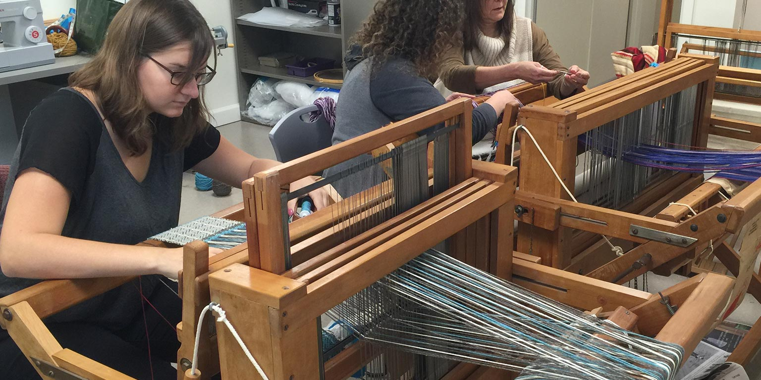 Student weaving using a large loom