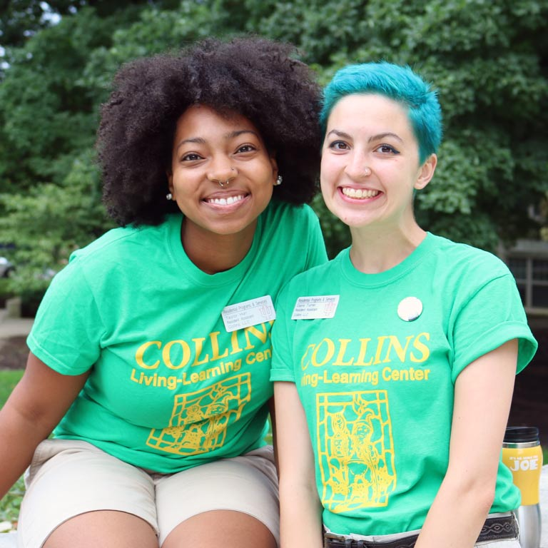 Two female students in Collins Center t-shirts smile and pose for the camera