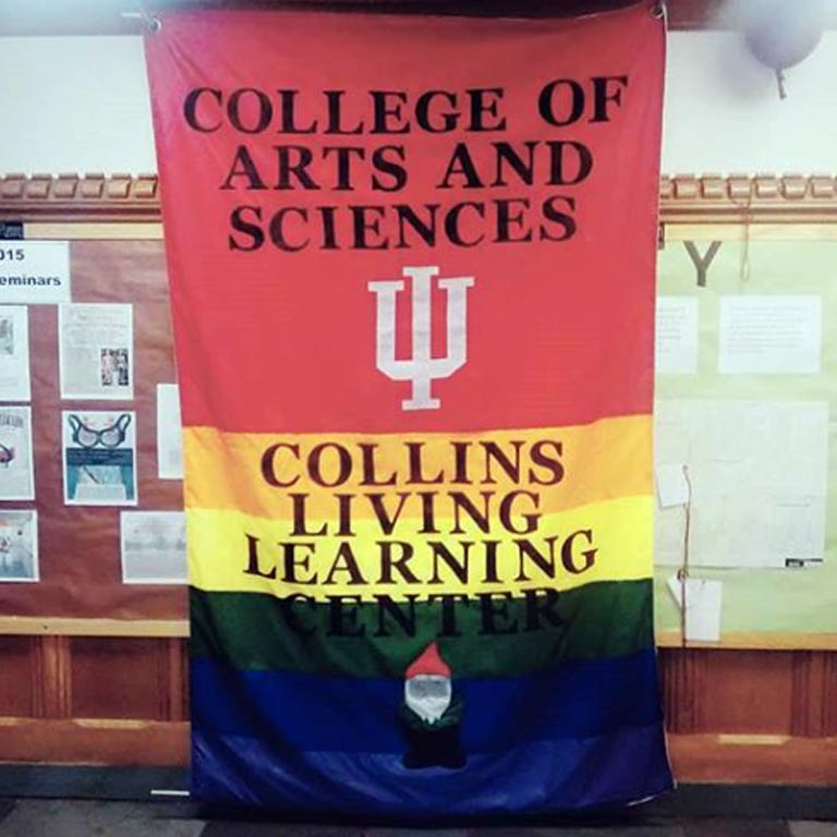 "Rainbow banner with the image of a gnome at the bottom that says, ""College of Arts and Sciences, Collins Living-Learning Center"""