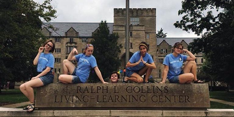 Five students posing with the Collins Living-Learning Center sign