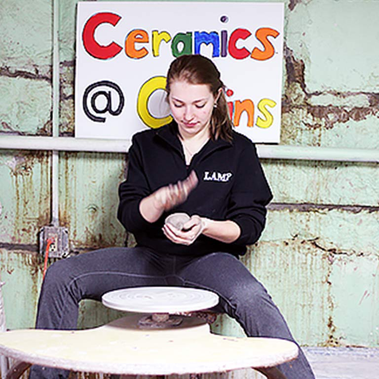 "Student making pottery in front of a sign that says, ""Ceramics at Collins"""
